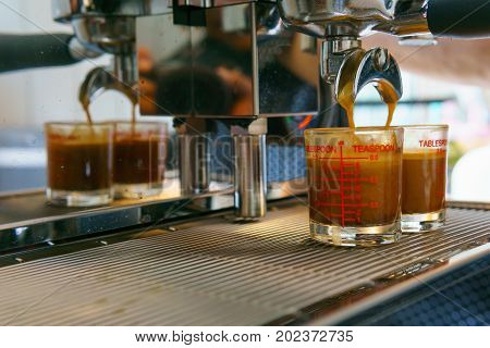 Close Up Of Espresso Coffee Pouring From Coffee Maker Machine To Glass Shot. Barista Coffee Brewing
