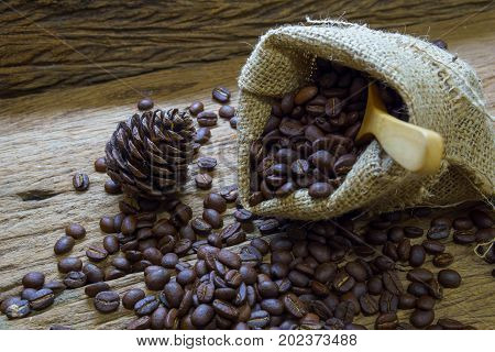 Pile Of Medium Or Dark Roasted Coffee Beans And White Cup With Wooden Spoon And Sackcloth Bag On Old