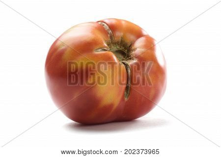Imperfect red ripe organic tomato isolated closeup