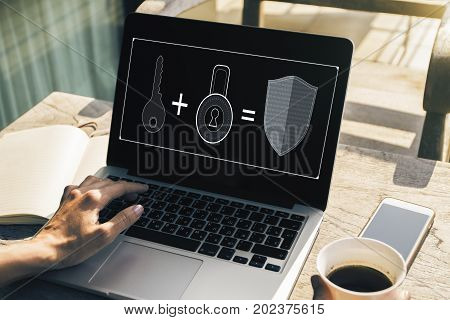 Female hands using laptop with antivirus interface on screen and holding coffee cup placed on cafe table with other items. Fraud concept