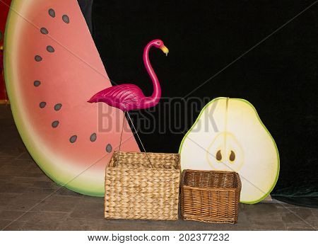Background with a pink flamingo on a dark green background. Flamingo watermelon and pear. woven baskets. Flamingo