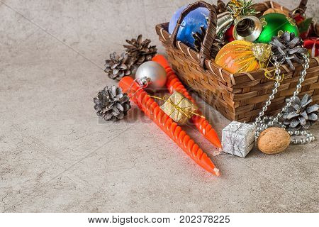 Preparing for Christmas. Wicker brown basket with Christmas toys cones red twisted candles and small shiny boxes with gifts on a gray background.