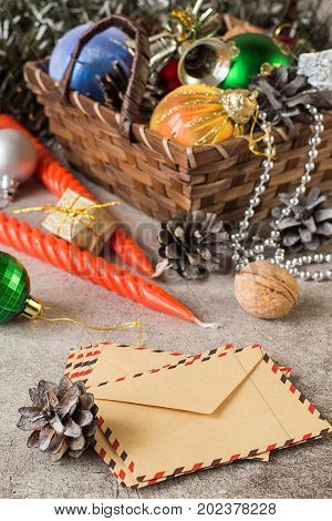 Preparing for Christmas. Wicker brown basket with christmas toys cones red twisted candles small shiny boxes with gifts and paper mail envelopes on a gray background.