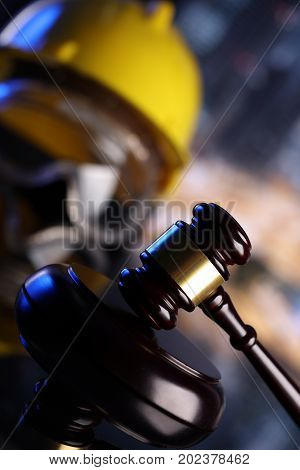 Construction law. Helmet and gavel. Colorful bokeh with buildings under construction.