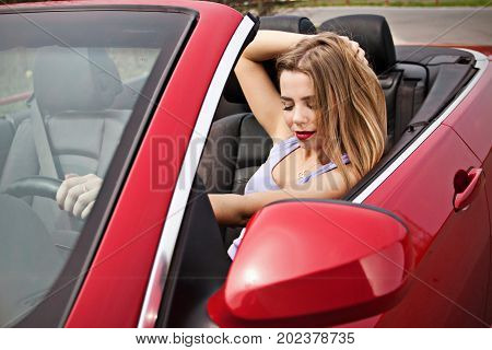 pretty young girl with red lips in red cabrio