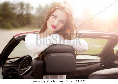 young pretty girl in red cabrio in sunlight