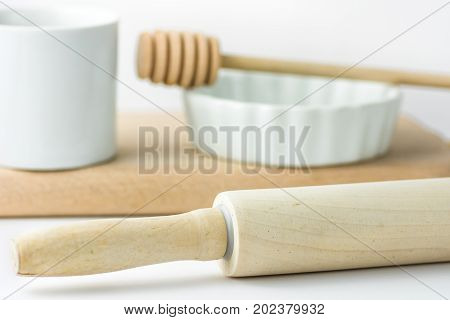 Wooden rolling pin white measuring cup baking form and honey dipper on cutting board. White tabletop background. Clean minimalist styled image. Template for menu banner card. Copy space.