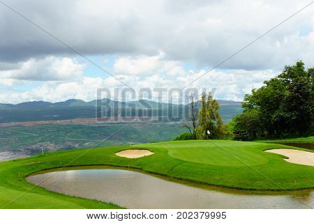 beautiful idyllic green of golf course with sand trap near mountain with blue sky and cloud in sunny day.
