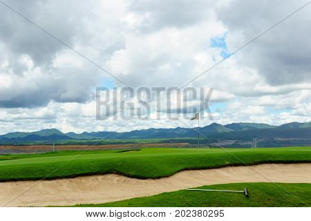 beautiful idyllic view green with sand trap and white flag and view of mountain blue sky with clouds
