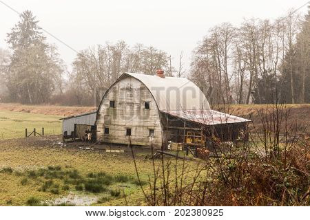 Weathered old barn building in rainy Pacific Northwest landscape.