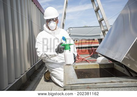 A professional in protective uniform, mask, gloves in the roof for cleaning
