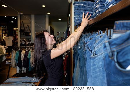 Seller in jeans store shows pair of jeans