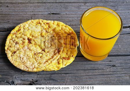 Whole grain crispbreads with glass of juice on old wooden table.Puffed crispbreads.Rice and corn crispbreads.Healthy breakfast or diet concept.Selective focus.