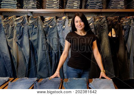 seller in jeans store shows pairs of jeans
