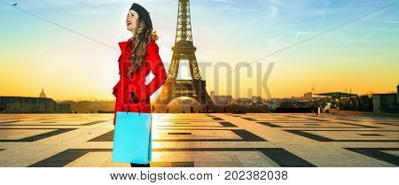 Bright in Paris. Full length portrait of smiling stylish woman in red coat against Eiffel tower in Paris France with shopping bag looking into the distance