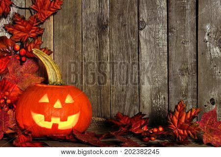 Halloween Jack O Lantern With Corner Border Of Autumn Leaves On A Rustic Wooden Background