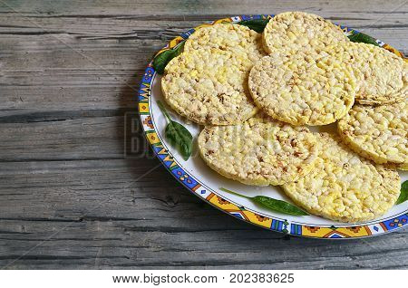 Whole grain crispbreads with spinach leaves on a plate on old wooden table.Puffed crispbreads.Rice and corn crispbreads.Healthy breakfast or diet concept.