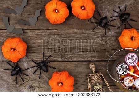 Rustic Halloween Frame Of Pumpkin Decor, Spiderwebs And Candy, Flat Lay Over A Wood Background