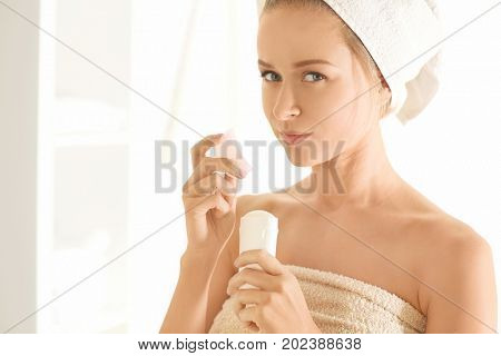 Beautiful young woman with deodorant at home poster