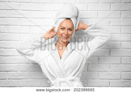 Beautiful young woman after shower on white brick wall background