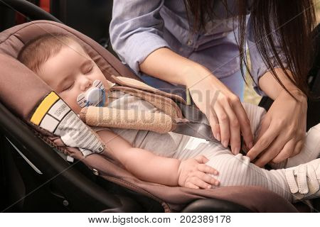 Mother fastening sleeping baby to child safety seat inside of car