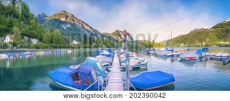 Panoramic view of the port from Weesen in Switzerland with lots of small boats docked to a pontoon surrounded by the Alps mountains and forest.