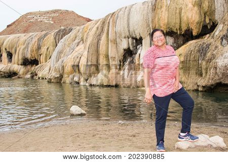 Asian woman posing by a gethermal terrace in Hot Springs State Park, Thermopolis, WY