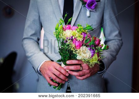 Groom holding flower bouquet for the bride