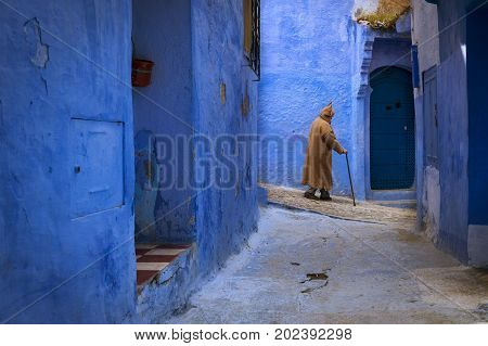Chefchaouen Morocco - April 10 2016: Moroccan man walking in a narrow street in the town of Chefchaouen in Morocco North Africa