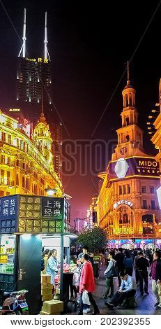 Shanghai, China - Nov 5, 2016: Night scene along Nanjing Road Pedestrian Street - Buildings with colorful lights in western architectural designs. People on the street.