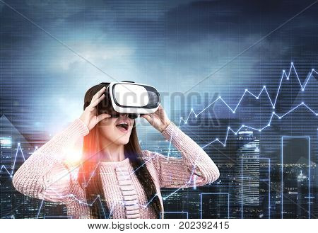 Close up portrait of a young woman wearing a pink cardigan and VR glasses. She is amazed by what she is seeing. She is standing against a night city background. Graphs. Toned image double exposure