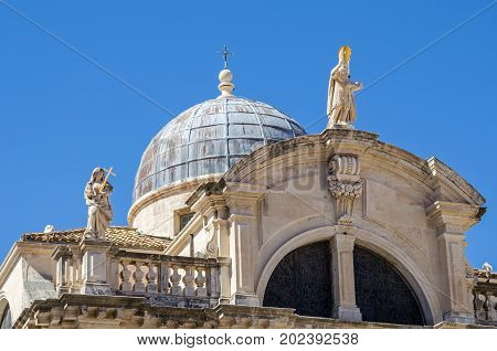 Top of the facade of the baroque Church of St. Blaise in the old city of Dubrovnik with the Statue of Saint Blaise the patron of the city and a personifications of Faith to the left on the balustrade. The saint shows in his left hand a scale model of the