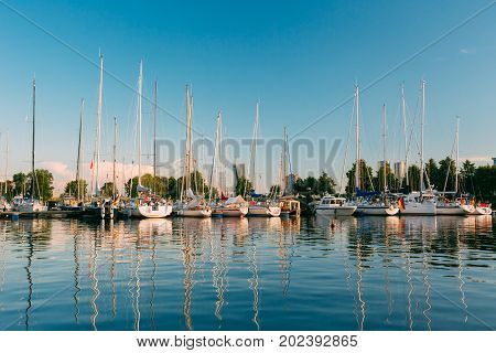 Riga, Latvia. Many Yachts Moored At The City Pier Harbour And Quay In Summer Sunny Evening. Reflections From Boats In The lear Water Of Western Dvina River.