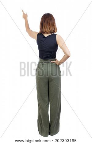Back view of  pointing woman. beautiful girl. Rear view people collection.  backside view of person.  Isolated over white background. Girl in green pants shows her hand up