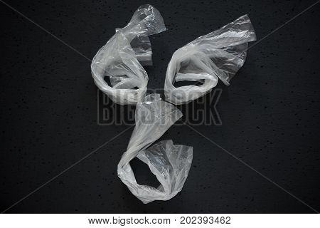Face Laid Out Of Empty Plastic Bags On A Dark Background. The Concept Of Consumption And Pollution O