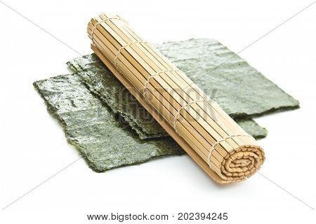 Green nori sheet and bamboo mat isolated on white background.