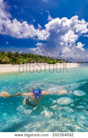 Tropical island with sandy beach overwater bungalows and tourquise clear water Maldives