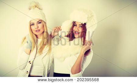 Fashion winter outfit concept. Two girls blonde and mulatto in warm white clothing having fun. Attractive women wearing fur caps scarfs gloves.