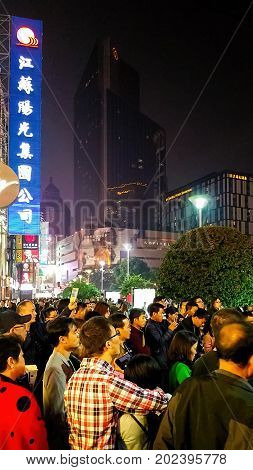 Shanghai, China - Nov 5, 2016: Night scene along Nanjing Road Pedestrian Street - Buildings with colorful lights in western architectural designs. Masses of people on the street.