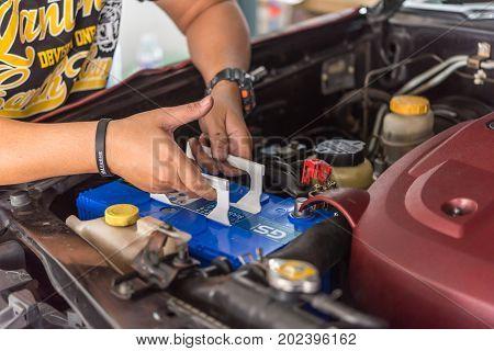 Checking A Car Battery For Repair At Car Garage