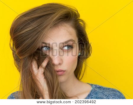 Portrait of a beautiful positive young woman while playing with her long silky hair isolated on yellow background