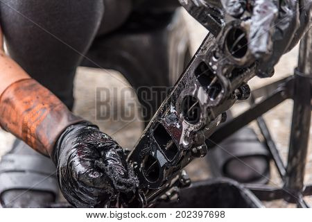 Car mechanic or serviceman disassembled car dirty engine for cleaning fuel injection and air flow system engine parts for fix and repair problem at car garage or repair shop