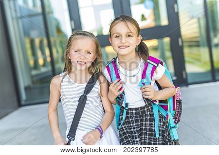 Two great girls Standing Outside School With Book Bags