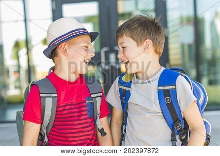 Some Boys Standing Outside School With Rucksack