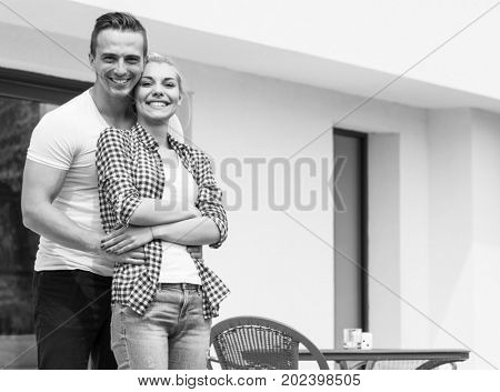 Happy two young lovers standing in front of modern house while smiling and huging