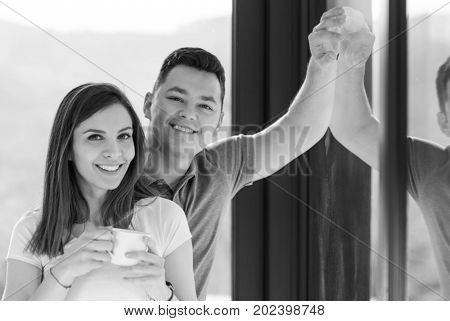 Happy two young lovers standing in living room and smiling while drinking coffe