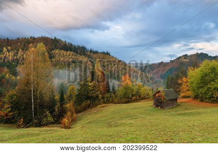 Autumn in a mountain village. Landscape with a wooden shed for hay. Evening with beautiful clouds. Carpathians, Ukraine, Europe