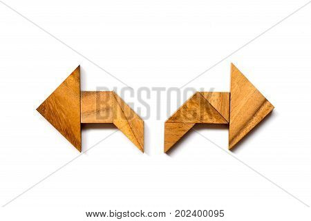 Wooden tangram puzzle in directioinal arrow shape on white background (Concept of making decision)