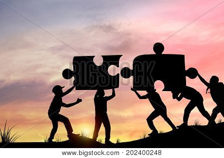 Silhouette people helping to connect jigsaw and puzzle to success concept as improving and development business