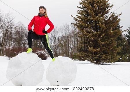 Outdoor sport exercises sporty outfit ideas. Woman wearing warm sportswear training exercising outside during winter. Having fun while making snowman